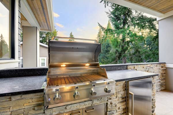 Outdoor kitchen with built in grill and stacked stone surround