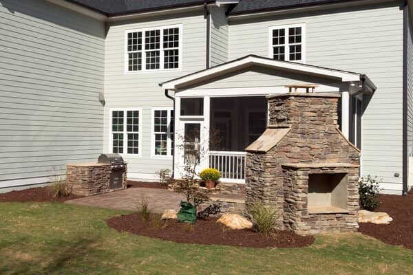 Outdoor stone fireplace and grill on concrete patio