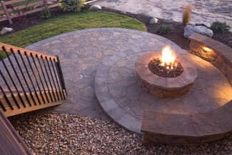 New spiral design stone paver patio with outdoor fire pit and stone seating area